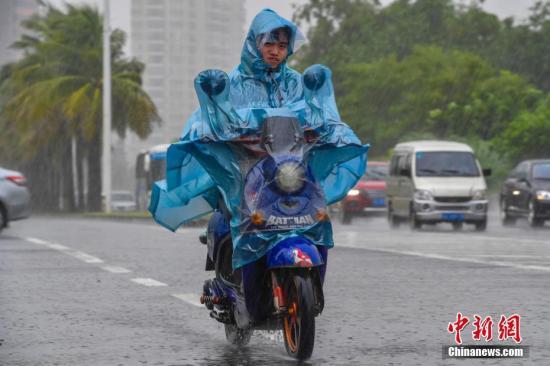 7月18日,海口居民冒雨出行。中新社记者 骆云飞 摄