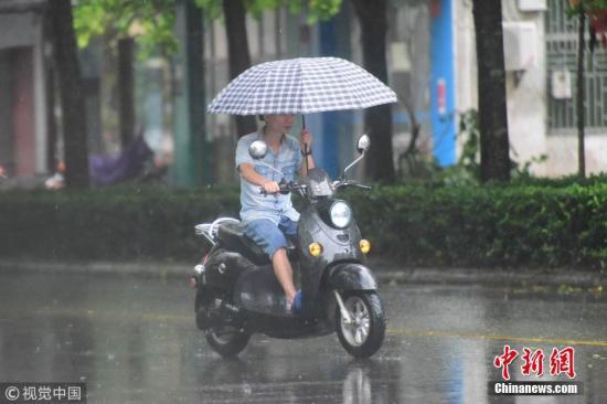 """图为台风""""山神""""登录前,海南琼海市民在大雨中出行。 图片来源:视觉中国"""