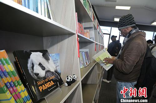 """当地时间7月17日,""""感知中国""""2018南非""""中国主题图书展""""活动在约翰内斯堡大学图书馆开幕。图为当地民众在展位前驻足观看。中新社记者 王曦 摄"""