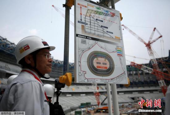 资料图:内地时间2018年7月18日,日本东京,凤凰城要,工人们正在加紧建树2020年东京奥运会和残奥会的主体育场,当天气温高达43.1摄氏度。