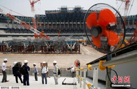 资料图:当地时间2018年7月18日,日本东京,工人们正在加紧建设2020年东京奥运会和残奥会的主体育场,当天气温高达43.1摄氏度。
