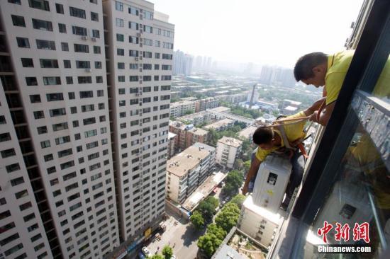 资料图:工作人员正在安装空调。/p中新社记者 张云 摄