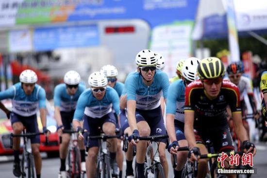 """7月23日,""""碧桂园杯""""2018第十七届环青海湖国际公路自行车赛在细雨中为民众带来""""速度与激情""""的盛宴。第二赛段西宁绕圈赛,选手们共骑行8圈,每圈14.4公里,全程115.22公里。本赛段分别在第二、四、六圈设置了三个途中冲刺点。最终,法国马赛车队43号琼斯·布伦顿在队友的配合下率先撞线,以2小时32分51秒的成绩拿下赛段冠军,同时获得象征个人总成绩第一的黄衫和冲刺积分第一的绿衫。来自青海天佑德队215号李自森成功保住象征""""亚洲最佳""""的蓝衫。中新社记者 马铭言 摄"""