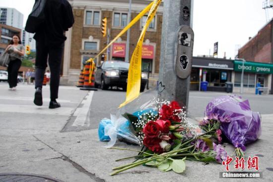 加拿大最大城市多伦多在当地时间7月22日夜间发生恶性枪击事件。截至23日傍晚6时,事件已导致2名受害者死亡,13人受伤。枪手也在事发现场身亡。图为案发地段、多伦多市中心以东的希腊城(Greektown)街区23日下午仍处于警方封锁状态,有民众在警戒线外为事件中的无辜受害者献上鲜花。这是今年以来多伦多一系列枪击事件中死伤人数最多的一起。中新社记者 余瑞冬 摄
