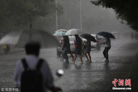资料图:大雨中撑伞走过的行人。图片来源:视觉中国