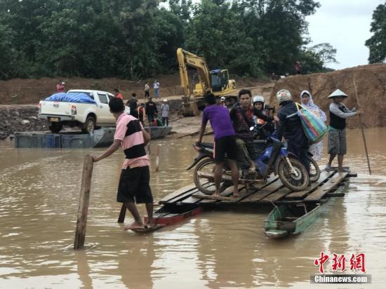 当地时间2018年7月25日,老挝阿速坡省Sanamxai,色贡河水位上涨,民众使用简易木筏过河。老挝南部阿速坡省一水电站23号晚发生溃坝事故,已导致数人死亡、数百人失踪。附近6个村庄被淹没,其中两个村庄受灾最为严重,超过6600人因洪水无家可归。