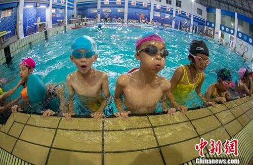 7月26日,学童们在江西新余市体育中心游泳馆学习游泳。入伏以来,江西高温范围明显扩大,多地最高气温超过38℃,未来一周,该省仍持续晴热高温天气。各地游泳场馆吸引了更多的中小学生,在此学习新技能,清凉度夏。中新社发 赵春亮 摄