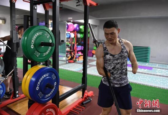 7月27日,倪敏成正在整理健身器材。倪敏成是浙江金华人,在他9岁时因意外事故失去双手,但他通过后天努力,获得2010年中国残疾人自行车锦标赛场地自行车团体赛冠军等多个国家级体育赛事冠军,如今他成为一名健身教练,用顽强意志对抗不公命运。中新社记者 王刚 摄