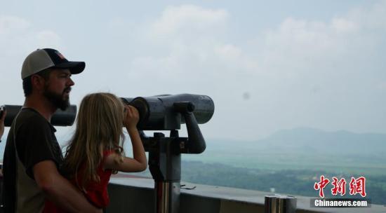 7月27日是朝鲜战争停战协定签订65周年纪念日。在韩国京畿道临津阁,游人如织,这里是民众可自由前往的韩国境内最北端。当天,记者探访了非军事区(DMZ)等地。图为游客在非军事区的一个瞭望台远眺朝鲜。中新社记者 曾鼐 摄