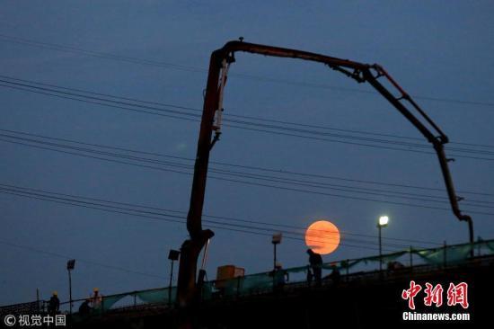 7月27日,江苏省淮安市,建筑工人在月全食前期的红月下施工,构成一幅优美的剪影。周长国 摄 图片来源:视觉中国