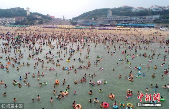 7月28日,人们在江苏省连云港市连岛海滨浴场消暑纳凉。 王健民 摄 图片来源:视觉中国