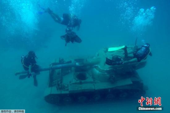 当地时间7月29日,黎巴嫩西顿,潜水员们在被沉到海底的坦克附近作业。黎巴嫩军队捐赠了六辆旧坦克和另外四辆军用车辆,将它们沉到海底作为人造礁石,形成有利于珊瑚礁生长和繁殖的人造栖息地。人造礁石的建设旨在恢复西顿海岸附近的海洋生态,并吸引游客和潜水爱好者。