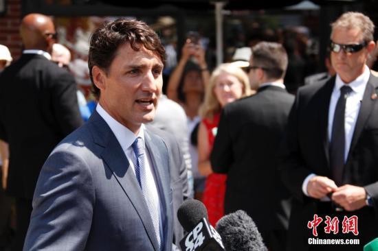 """当地时间7月30日,加拿大总理贾斯廷・特鲁多在多伦多参加""""7・22""""恶性枪击案遇难者葬礼,并到案发地希腊城街区献花悼念遇难者。该起枪击案已导致2人遇难、13人受伤,是今年以来多伦多一系列枪击事件中死伤人数最多的一起。图为特鲁多对媒体表示,当局正在从各方因素考量,以作出可以保障社区安全的长期决策。 中新社记者 余瑞冬 摄"""