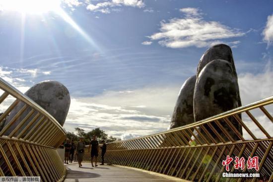 越南岘港佛手桥爆红网络游客。图为游客从巨大的掌心上穿过。