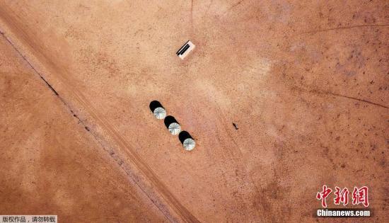 当地时间7月20日,新南威尔士州沃尔格特镇的郊区,一位农夫走在水槽和水箱旁。