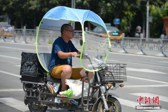 资料图:男子在电动车上撑起遮阳棚。<a target='_blank' href='http://www.chinanews.com/'>中新社</a>记者 刘文华 摄