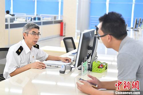 资料图:一男子在广州南沙海关报关大厅办理报关业务。 /p中新社记者 陈骥旻 摄