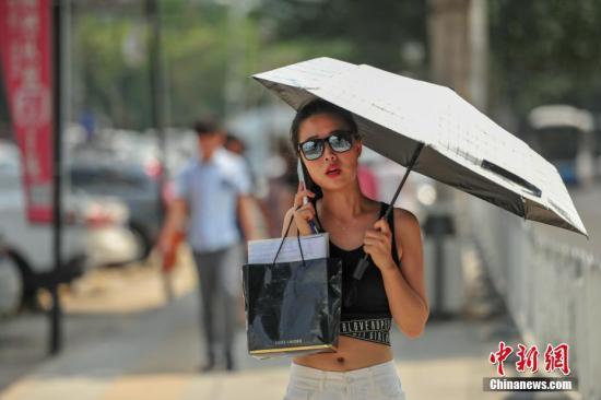 8月3日,市民在高温天气出行。中新社记者 于海洋 摄