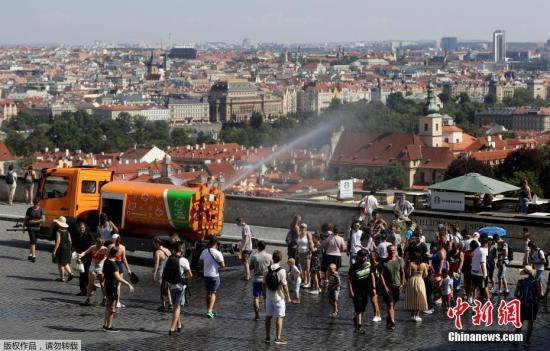 在捷克首都布拉格,37℃的高温让人们聚集在一辆洒水车旁,这台车是专门用来向行人喷水,提供降温服务的。