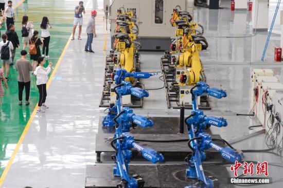8月3日,长沙,众多机器人在厂房内集体跳舞。这些机器人由长泰机器人研制,兼具高速度与高精度双重优点及灵活的机械手腕,是一款低成本高性能的六轴轻型机器人,重复定位精度可达0.05毫米。<a target='_blank' href='http://www.chinanews.com/'>中新社</a>记者 杨华峰 摄