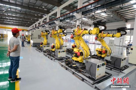 8月3日,长沙,众多机器人在厂房内集体跳舞。这些机器人由长泰机器人研制,兼具高速度与高精度双重优点及灵活的机械手腕,是一款低成本高性能的六轴轻型机器人,重复定位精度可达0.05毫米。中新社记者 杨华峰 摄