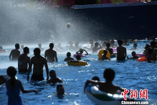 图为游客在水中玩球。陈超 摄