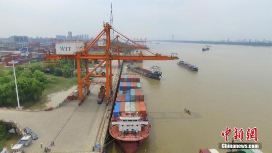 """阳逻武汉新港位于武汉天兴洲以东70公里的长江岸线上,是中国最大内河航运港口。2017年底建成的铁水联运一期工程实现了铁路贯通集装箱港区的零突破,航运向东入海、班列向西入欧。2108年2月阳逻港铁水联运二期、三期工程通过评审。项目建成后,阳逻港铁水联运能力将由目前10万标箱提升至210万标箱,成为中国内陆地区规模最大的铁水联运枢纽港,真正打通了长江中游航运中心""""铁水联运""""最后一公里的瓶颈。形成以阳逻集装箱核心港为主体,与吴家山集装箱铁路中心站、滠口货场形成""""一线串三珠""""格局,实现武汉地区江海直达、汉欧班列、商贸物流3种集装箱运输方式的有效集并运转。图为航拍铁水联运枢纽阳逻国际港。 中新社记者..."""