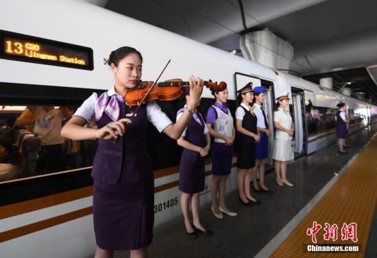 """8月5日,乘务员们身着不同时代制服在""""复兴号""""前迎接旅客。当日,系浙江杭州""""西子号""""品牌列车30周年的""""生日"""",从1988年的81/82次特快列车到如今的G20次""""复兴号""""动车组,""""西子号""""品牌列车不断提速、升级,见证了中国铁路的快速发展。 中新社记者 王刚 摄"""