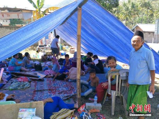 地震发生后,大批灾民在地震后前往庇护中心暂时栖身。由于印尼当局在上周地震后已收容约一万人,这使得庇护中心物资紧张,军方和红十字会人员加紧分发物资。图为村民在村子空地上分散安置。 林永传 摄
