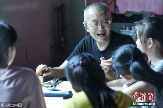 """资料图:杭州""""爷爷老师""""自学成才,菜摊义务教孩子们学英语。图片来源:视觉中国"""