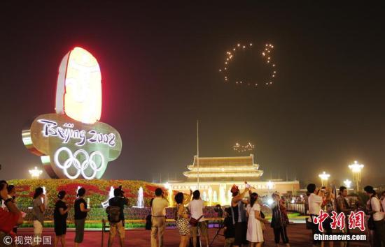 """2008年8月8日,天安门广场上空燃放北京奥运会开幕式焰火《历史足迹》,烟花组成的""""大脚印""""在夜空绽放,在全世界的注视下,一步步走向鸟巢。 图片来源:视觉中国"""