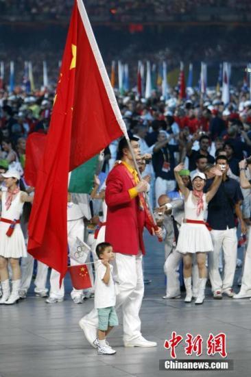 """汶川地震和奧運會是2008年的關鍵詞,在北京奧運會開幕式上,中國代表團的旗手是著名籃球運動員姚明,走在姚明身邊的是獲得""""汶川地震小英雄""""光榮稱號的四川省阿壩州映秀鎮漁子溪小學二年級學生林浩。中國體育代表團派出了1099人的龐大陣容,參加全部28個大項的比賽。 <a target='_blank' href='http://www.itlfmzi.cn/'>中新社</a>記者 杜洋 攝"""
