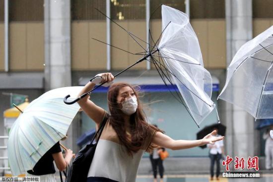 """当地时间2018年8月8日,台风""""姗姗""""逼近日本,东京民众用雨伞抵挡暴雨和大风。因风力过大,街上行人的雨伞在风中呈现各式造型。"""