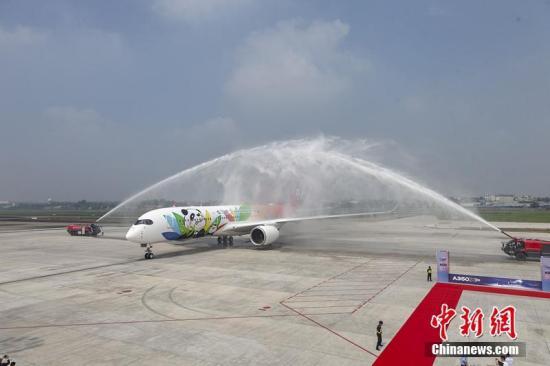 """8月9日上午,历经10小时的空中飞行,四川航空首架身披熊猫彩绘新装的空客A350飞机顺利抵达成都双流国际机场,川航由此成为中国内地首批接收A350飞机的航空公司之一。川航A350飞机是""""史上最萌""""的客机,机身涂装8只俏皮可爱的卡通大熊猫,让科技范儿十足的A350客机充满呆萌欢乐的色彩,极具四川地域特色。川航表示,未来将在该飞机上推出""""熊猫之旅""""主题航班,客舱环境、餐饮供应、服务流程上将会呈现出大量的""""熊猫""""元素。图为""""过水门""""仪式,寓意接风洗尘。 钟欣 摄"""