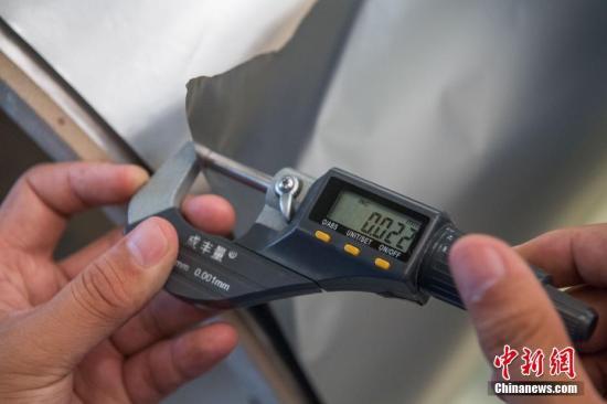 8月8日,山西省太原市,太钢精密带钢公司工作人员用精密仪器测量厚度为0.02毫米的不锈钢。这种厚度为0.02毫米,宽度达600毫米的不锈钢于日前开始量产,预计月产量达到3000公斤左右,主要应用在航空航天、石油化工、汽车、电子、家电、计算机等领域。在此之前,该产品因工艺控制难度大,长期被日本、德国等国家垄断。 <a target='_blank' href='http://www.chinanews.com/'>中新社</a>记者 韦亮 摄
