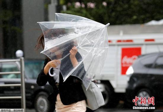 資料圖:臺逼近日本,東京民眾用雨傘抵擋暴雨和大風。因風力過大,街上行人的雨傘在風中呈現各式造型。