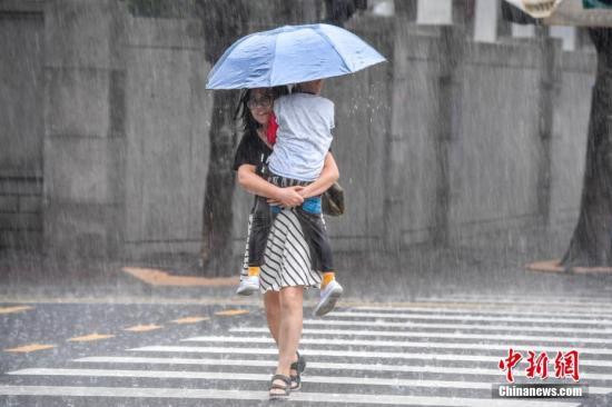 8月10日9时,南海热带低压在海南省琼海市潭门镇沿海登陆,登陆时中心附近最大风力有7级(15米/秒),中心最低气压998百帕。受其影响,海南岛大部出现大到暴雨,局部降特大暴雨的强降雨天气,海南全省平均面雨量为101.8mm。海口市区多路段出现积水,对民众生产、生活带来影响。图为一位母亲抱孩子冒雨出行。 骆云飞 摄