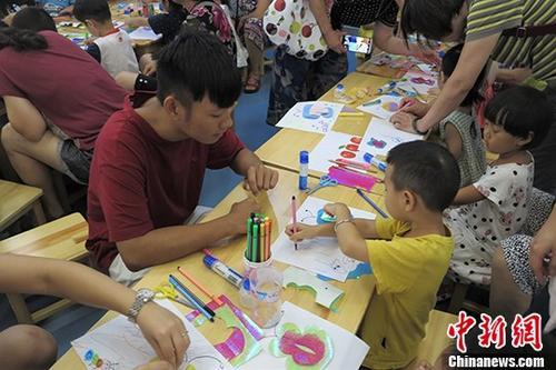 资料图为台湾实习生们在2018注册送体验金68首都图书馆少儿阅览室教小朋友做手工。 <a target='_blank' href='http://www.chinanews.com/'>中新社</a>记者 李晗雪 摄