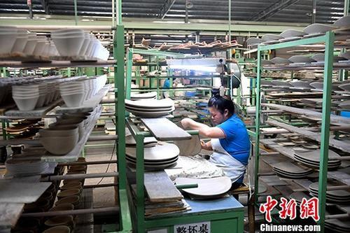 """祸建德化县""""天下陶瓷之皆""""的称呼。图为德化一陶瓷公司的消费车间。(材料图片)a target='_blank' href='http://www.chinanews.com/'中新社/a记者 吕明 摄"""