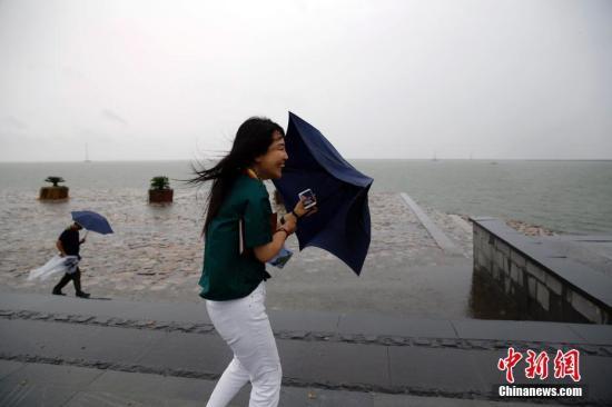 资料图:民众顶风出行。中新社记者 汤彦俊 摄