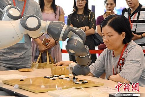 """资料图片:一名围棋爱好者与一台名为""""小智""""的人工智能机器人对弈。 <a target='_blank' href='http://www.chinanews.com/'>中新社</a>记者 钟建珊 摄"""