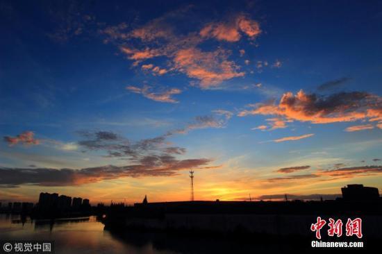 """2018年8月14日早晨,浙江绍兴,台风""""摩羯""""过境后,市区上空出现一片美丽的火烧云。 图片来源:视觉中国"""