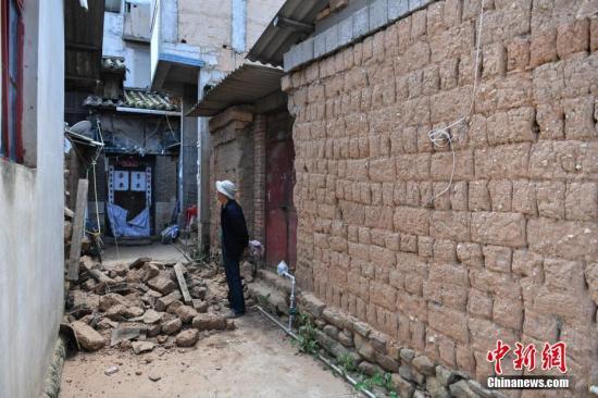 资料图:8月14日,一老人查看被地震损坏的房屋。 中新社记者 任东 摄