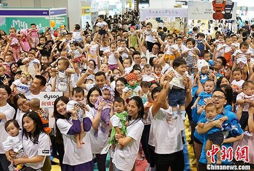 8月14日,香港特区政府统计处公布,今年年中香港人口临时数字为7,448,900人,比去年增加57,200人,增长率0.8%。图为本月初香港年轻父母与未满周岁的婴儿出席活动。 <a target='_blank' href='http://www.chinanews.com/'>中新社</a>记者 张炜 摄