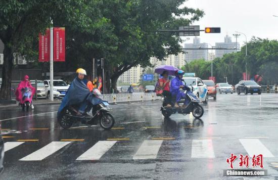 资料图:在暴雨中出行的海口市民。 吴天军 摄
