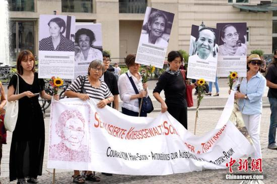 """资料图:8月14日是国际""""慰安妇""""纪念日。当天,旅德的韩国和日本民间团体在柏林举行集会,要求日本政府向""""慰安妇""""制度暴行受害者正式道歉,并作出赔偿。图为当天下午,抗议者在德国柏林市中心勃兰登堡门前高举受害者照片和证言。<a target='_blank' href='http://imozar.com/'>中新社</a>记者 彭大伟 摄"""