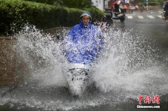 """8月17日,南京街头的一名男子骑车从积水中冲过。当日,受台风""""温比亚""""登陆影响,江苏多地迎来狂风暴雨。 泱波 摄"""