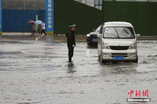8月20日,一名交警在积水路段指挥交通。当日下午,青海西宁突降大雨,市区部分街道积水严重,市民出行困难,西宁市气象台发布暴雨黄色预警。 中新社记者 李培源 摄