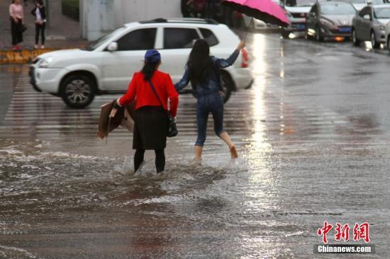 资料图:民众在降雨中出行。 /p中新社记者 李培源 摄