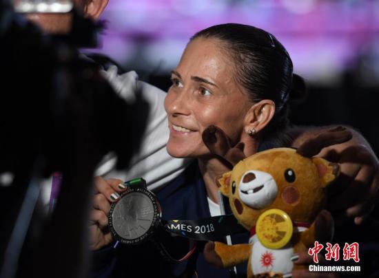 """8月23日,雅加达亚运会体操女子跳马决赛,乌兹别克斯坦选手奥克萨娜·丘索维金娜以14.287分获得一枚银牌。现年43岁的丘索维金娜此前为了给患白血病的儿子筹款治病,曾代表不同国家多次参加体操世锦赛和奥运会,如今儿子已经康复,""""体操妈妈""""再次代表乌兹别克斯坦参加雅加达亚运会,继续其体操梦想。图为丘索维金娜赛后展示自己的银牌。<a target="""